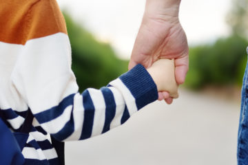 Stock photo of parent and child hand in hand
