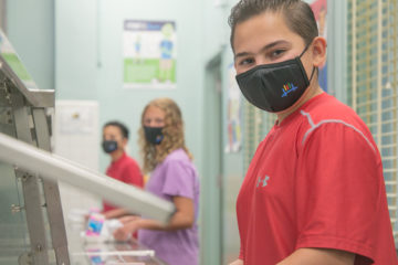 Photo of children with face masks social distancing in a cafeteria line