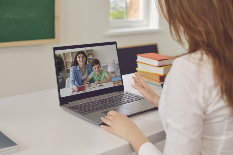 Stock image of parent and child chatting with teacher virtually