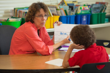 GRASP educator works with student in classroom.
