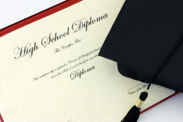 High school diploma and black cap with tassle