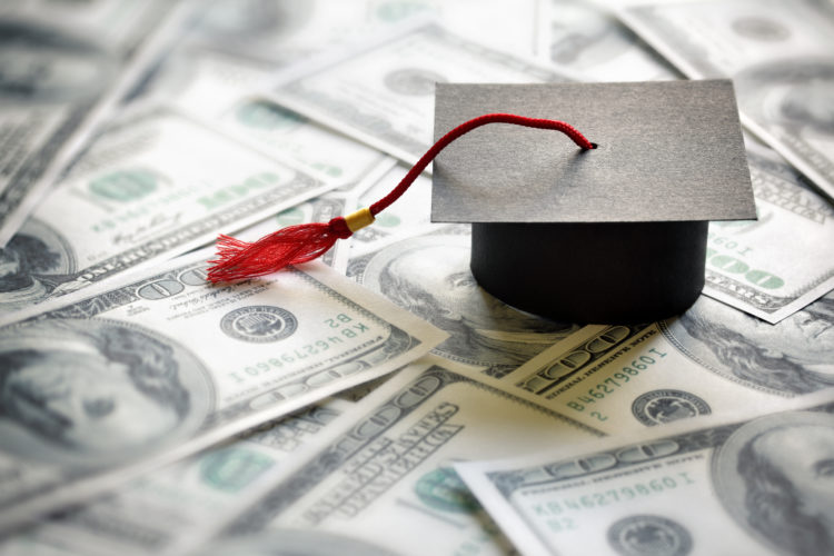 Stock photo of a graduation cap on top of dollar bills